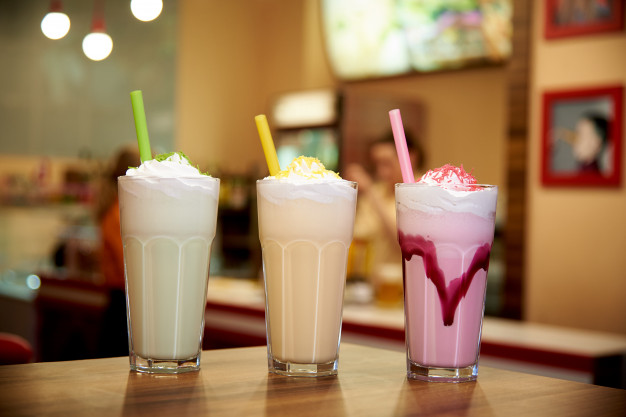 milk-shakes-with-straws-wooden-table-cafe_83055-504